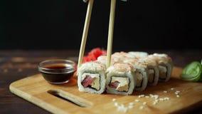 Sushi freschi, rotoli sulla tavola Fondo scuro Bastoni dei sushi video d archivio