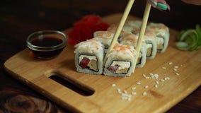 Sushi fresco, rollos en la tabla Fondo oscuro Palillos del sushi almacen de metraje de vídeo