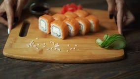Sushi fresco, rollos en la tabla Fondo oscuro Palillos del sushi almacen de video