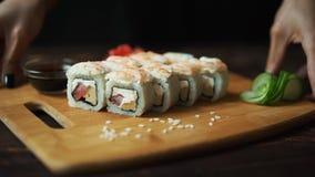 Sushi fresco, rollos en la tabla Fondo oscuro Palillos del sushi metrajes