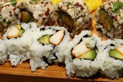 Sushi Fusion Rolls on a platter. A group of avocado, crab sushi appetizers on a wood platter seen at a party Stock Photography