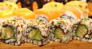 Sushi Fusion Rolls on a platter. A group of avocado, yellowtail sushi appetizers on a wood platter seen at a party Royalty Free Stock Images