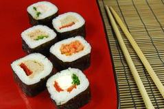 Sushi futomaki with chopsticks. Sushi futomaki on red plate with chopsticks stock photo