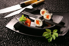 Sushi futomaki. Typical Japanese food with knives on a black background Stock Photography