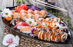 Sushi gesetztes nigiri und Sushirollen verziert mit Blumen auf Bambushintergrund Lizenzfreie Stockfotos