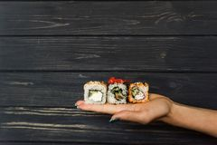 Sushi on the hand of a girl Stock Image