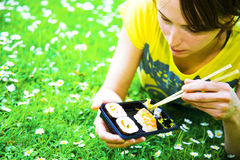 Sushi girl. Pretty girl eating take-away sushi in a park Royalty Free Stock Photos