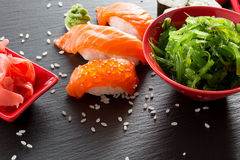 Sushi and green seaweed salad on a slate table Stock Photo