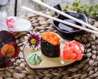 Sushi Gunkan maki with salmon caviar on plate in the form of heart on bamboo mat, selective focus. Japanese cuisine royalty free stock photos