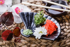 Sushi Gunkan maki with seaweed, sesame and cream cheese on black plate on bamboo mat decorated with flowers. Japanese cuisine. Stock Images