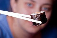 Sushi humano da tomada por chopsticks imagem de stock royalty free