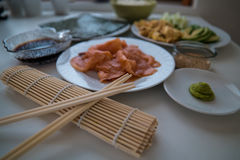 Sushi - Ingredients in bowls and chopsticks. Chopsticks, wasabi  and sushi rolls on a table Royalty Free Stock Image