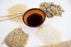 Sushi ingredients on white. Different types of asian rice, chopsticks, straw matt for rolls, soy sauce Stock Photography