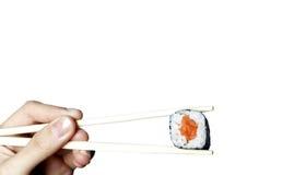 Sushi isolado nos chopsticks Fotos de Stock Royalty Free