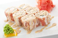 Sushi. Japanese Cuisine - Sushi Roll with Chicken and Cucumber inside. Bacon outside. Garnished with Sauce Stock Photo