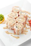 Sushi. Japanese Cuisine - Sushi Roll with Chicken and Cucumber inside. Bacon outside. Garnished with Sauce Royalty Free Stock Photography