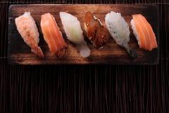 Sushi japanese food various wood tray flat top view dark background Royalty Free Stock Photos