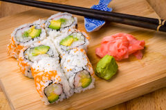 Sushi Kalifornien rollt Aperitif mit Reisavocado mit chopstic Lizenzfreies Stockbild