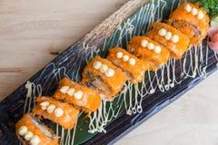 Sushi Kalifornien rullar på den svarta plattan - japansk mat Royaltyfri Fotografi