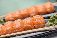 Sushi with a light-salted salmon, wooden sticks and sauce of wasabi on a ceramic dark plate. Sushi with a light-salted salmon, wooden sticks and green sauce of royalty free stock image