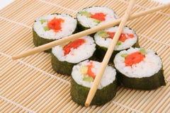 Sushi maki. Six pieces of sushi maki and chopsticks on a bamboo mat royalty free stock photo