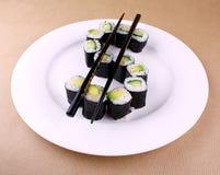 Sushi maki als Dollarzeichen auf weißer Platte Stockfoto