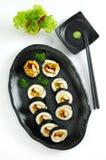Sushi maki auf schwarzer Servierplatte mit Wasabi und Kopfsalat lizenzfreie stockbilder