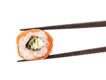 Sushi maki. In chopsticks. Isolated on white background royalty free stock photography