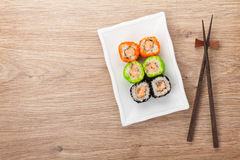 Sushi maki. And chopsticks on wooden table. View from above with copy space stock photos