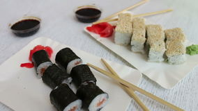 Sushi-maki delicioso com salmões e sushi com peixes, o gengibre cor-de-rosa, wasabi verde em uma placa e em um molho de soja em u video estoque
