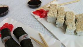 Sushi-maki delicioso com salmões e sushi com peixes, o gengibre cor-de-rosa, wasabi verde em uma placa e em um molho de soja em u filme