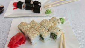 Sushi-maki delicioso com salmões e sushi com peixes, o gengibre cor-de-rosa, wasabi verde em uma placa e em um molho de soja em u vídeos de arquivo