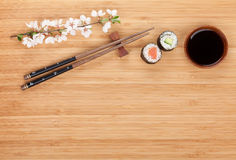 Sushi maki with fresh sakura branch over bamboo table Royalty Free Stock Images