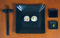 Sushi maki rolls on a tray. Sushi maki rolls presented on a plate with sauces and chopsticks royalty free stock photos