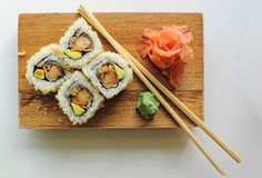 Sushi maki rolls with sesame seeds and avocado, with chopsticks, wasabi and ginger - close up view. Close-up view of maki sushi rolls on a wood block, with royalty free stock photo