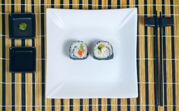 Sushi maki rolls on a tray. Sushi maki rolls presented on a plate with sauces and chopsticks royalty free stock images