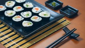 Sushi maki rolls on a tray. Sushi maki rolls presented on a tray with sauces and chopsticks stock images