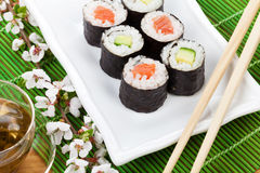 Sushi maki set, green tea and sakura branch Stock Photo