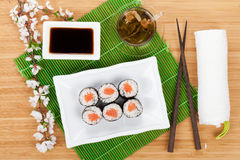 Sushi maki set, green tea and sakura branch Stock Photos