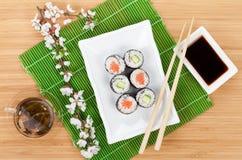 Sushi maki set, green tea and sakura branch Royalty Free Stock Image