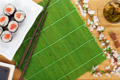 Sushi maki set, green tea and sakura branch Royalty Free Stock Photo