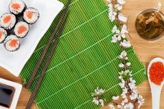 Sushi maki set, green tea and sakura branch Stock Photography