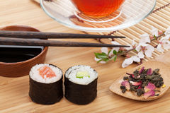 Sushi maki set, herbal tea and sakura branch Royalty Free Stock Image