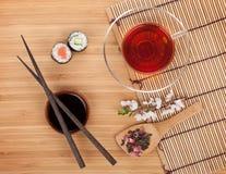 Sushi maki set, herbal tea and sakura branch Stock Photo