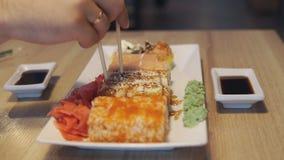Sushi mangeurs d'hommes réglés avec des baguettes sur le restaurant banque de vidéos