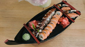 Sushi master pouring sushi rolls with unagi sauce stock video