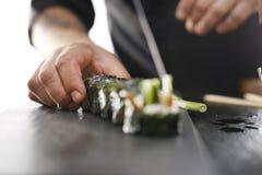 Sushi master prepares futomaki Stock Photos