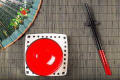 Sushi mat background with plates Royalty Free Stock Photo