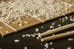 A sushi mat on which scattered rice next to lies chopsticks stock images
