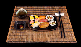 Sushi Meal For One. Single setting of sushi and tea on a bamboo mat isolated on black Stock Image